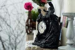 Statuetta nera dell'orologio, candelieri con le candele su un lig Fotografia Stock Libera da Diritti