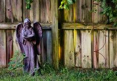 Statuetta variopinta del giardino contro il recinto stagionato fotografia stock