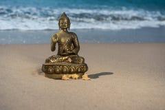 Statuette Βούδας χαλκού στην παραλία με τα κύματα στοκ φωτογραφία