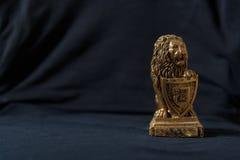 Statuette ενός χρυσού λιονταριού που κλίνει σε μια ασπίδα Μαύρη ανασκόπηση Στοκ Εικόνα