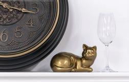 Statuette μιας γάτας στα πλαίσια ενός καφετιού ρολογιού και ενός γυαλιού κρασιού στοκ εικόνες