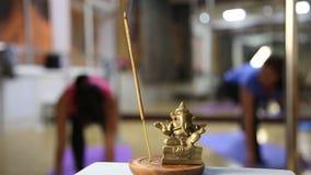 Statuette του ganesha και το άρωμα κολλούν, ομάδα γιόγκας γυναικών που ασκούν το στούντιο σε ένα θολωμένο υπόβαθρο απόθεμα βίντεο