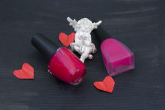 Statuette of an angel, paper hearts and two bottles of varnish on the black background Stock Photography