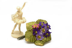 Statuette of a ballerina on a white background. Old porcelain figurine of a ballerina and artificial flower on a white background Stock Image