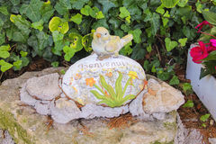 Statuette of a bird with the inscription. Benvenuti ( Welcome ) in the Italian garden Royalty Free Stock Photography