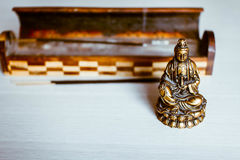 The statuette of the Buddha's blessing and incense. The statuette of the Buddha's blessing on a light background with Aromatic sticks Royalty Free Stock Photography
