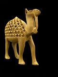 Statuette of a camel. Small wooden statuette of a camel on a black background stock image