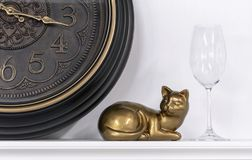 Statuette of a cat against the background of a brown clock and a wine glass stock photo