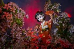 Statuette dancing geisha in the garden. Sakura with decorative lighting Stock Images