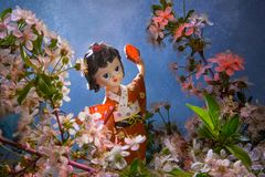 Statuette dancing geisha in the garden. Sakura with decorative lighting Royalty Free Stock Photos