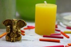 Statuette de Ganesh d'un dieu d'hindouisme sur la table grise avec la bougie jaune et les bâtons colorés Fond de table de station Photographie stock