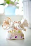 Statuette des colombes et des anneaux de mariage Photographie stock