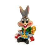 Statuette des grauen Kaninchens mit dem Geschenk lokalisiert auf einem weißen Hintergrund Stockfotografie