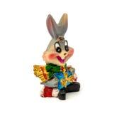 Statuette des grauen Kaninchens mit dem Geschenk lokalisiert auf einem weißen Hintergrund Lizenzfreie Stockbilder