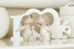 Statuette di piccoli angeli Due angeli con le lettere di legno bianche Immagini Stock