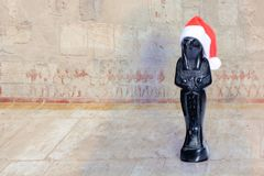 Statuette of the egyptian god Horus in a red Santa Claus hat stock photo