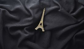 A statuette of the Eiffel Tower on a black fabric background. Top view stock image