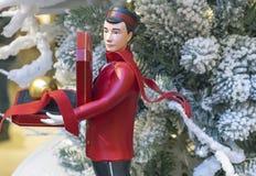 Statuette eines Hotelkuriers mit einem goldenen Weihnachtsball in einer Geschenkbox stockfoto