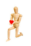 Statuette figure wooden man human makes shows experiences emotional action on a white background. In love with a heart in his hand. S stock images