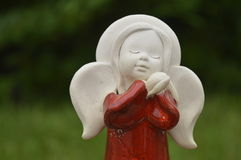 Statuette, figurine: beautiful angel. With folded hands under the cheek, red robe, red dress Stock Images