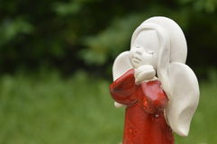 Statuette, figurine: beautiful angel. With folded hands under the cheek, red robe, red dress Royalty Free Stock Photo