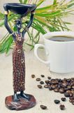 Statuette of a girl and coffee. Statuette of a girl with dishes, cups and coffee beans Royalty Free Stock Photos