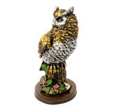Statuette of gold owl with flowers isolated on a white background. Photo of statuette of gold owl with flowers isolated on a white background stock photos
