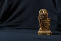 Statuette of a golden lion leaning on a shield. Black background. Stock Image