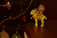 Statuette of a golden sheep on the background of a Christmas tree Royalty Free Stock Photos