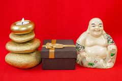 Statuette of a laughing Buddha with stones and a candle, and a gift box, on a red background, feng shui. Statuette of a laughing Buddha with stones and a candle royalty free stock photos