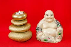 Statuette of a laughing Buddha with stones and a candle, on a red background, Feng Shui. Statuette of a laughing Buddha with stones and a candle, on a red royalty free stock photo