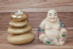 Statuette of laughing Buddha with stones and a candle, on a wooden background, Feng Shui. Statuette of laughing Buddha with stones and a candle, on a wooden royalty free stock images