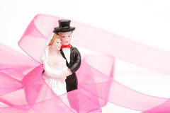 Statuette newly-married couple. With pink strip Royalty Free Stock Image