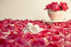 Statuette of two antique little lovely angels of the gypsum on the white background with red peony flower petals. Love, romantic, stock image
