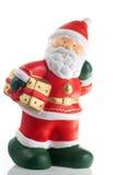 Statuette von Weihnachtsmann mit einem Geschenk Stockfotografie