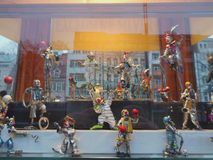 Statuettes of clowns. In a showcase with reflections of the city Stock Photo