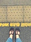 Status achter de gele lijn met sandals stock fotografie