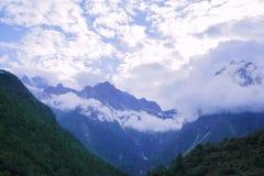 Status bij de bovenkant van de berg het letten op wolken stock foto's
