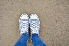 Status met twee hierboven schoenen op zand van stock afbeelding