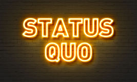 Status quo neon sign on brick wall background. Royalty Free Stock Images