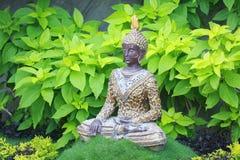 Status władyki Buddha obsiadanie w gazonie otaczającym zielonymi drzewami Obrazy Royalty Free