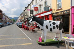 Statute of a black and white spotted cow, Dingle, Ireland. Whimsical cow statue welcomes visitors to a row of colorful shops and restaurants in Dingle, Ireland Royalty Free Stock Photos