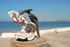Statute of dancing couple on the Malecón. A statute of a dancing couple stand on the Malecon in Puerto Vallarta, Mexico, next to the Pacific Ocean on a bright Stock Photos