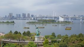 Statute of Liberty and Rainbow Bridge in Odaiba Seaside Park Tokyo. A view looking out into the harbor at Odaiba Seaside Park Tokyo. Enjoying the view of the Royalty Free Stock Photo