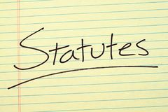 Statutes On A Yellow Legal Pad. The word `Statutes` underlined on a yellow legal pad Stock Images