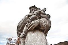 Staty av biskopen Nepomuk med ett kors på den gamla flodlahnbrien Arkivfoton