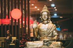 Staty av Buddhasammanträde i den Lotus Position With Raised Right armen arkivbilder