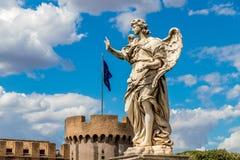 Staty av en ängel på den bakgrundsslottSant `en Angelo och flagga av europeisk union, Rome, Italien royaltyfria bilder