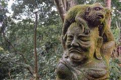 Staty av en apa som sitter på ett mänskligt huvud som täckas av mossa i den Sacret apaskogen i Ubud Bali arkivbilder
