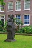 Staty av en Beguine i den härliga borggården av Begijnhofen på Amsterdam Arkivbilder